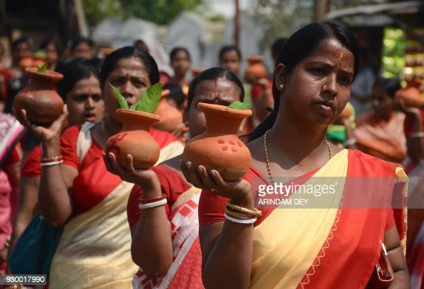 Indian Hindu devotees carry holy water on a pot to perform Yagya a ritual of devotion and worship in front of a sacred fire to restore peace and...