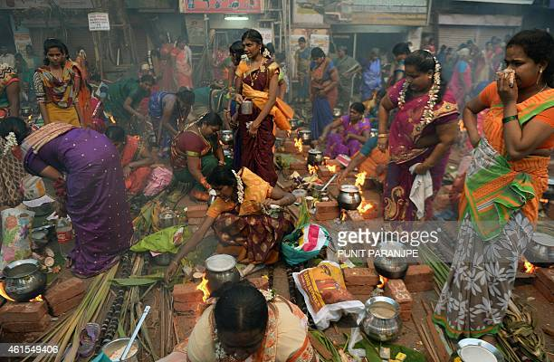 Indian Hindu devotees cook a traditional sweet dish on open fires during a community function on the occasion of Pongal in Mumbai on January 15 2015...