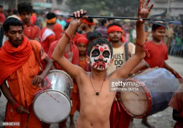 Indian Hindu devotees dance during the ritual of 'Charak' worship an old ritual observed on the last day of the Bengali calender year in Siliguri on...