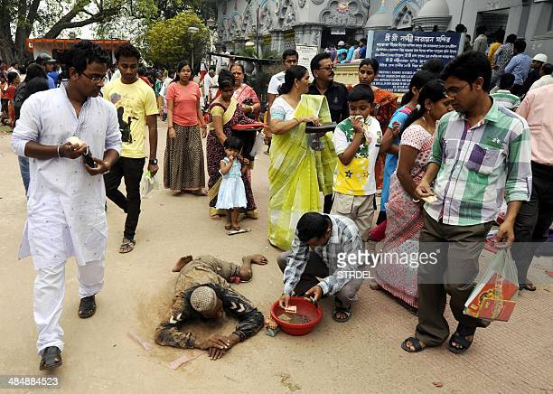 Indian Hindu devotees donate money to a disabled Muslim beggar after offering prayers at a temple in Agartala on April 15 during Bengali New Year...