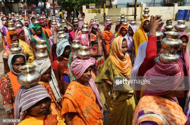 Indian Hindu devotees from a tribal community carry pots as they take part in a religious procession as part of the Manda festival at a Shiva temple...