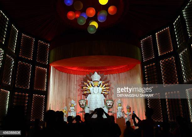 Indian Hindu devotees gather in front of a puja pandal an area to worship the Hindu Goddess Durga ahead of the forthcoming Durga Puja festival in...