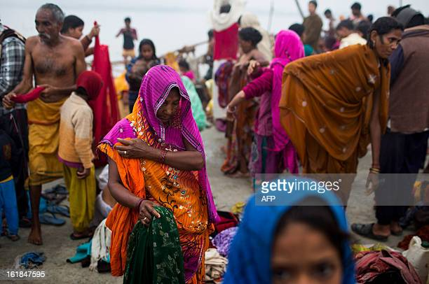 Indian Hindu devotees get dressed after bathing at the Sangam or confluence of the Yamuna Ganges and mythical Saraswati rivers at the Kumbh Mela in...