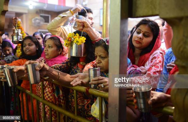 Indian Hindu devotees hold cups of milk and water as they pay their respects on the occasion of Navratri festival at a temple in Amritsar on March 18...