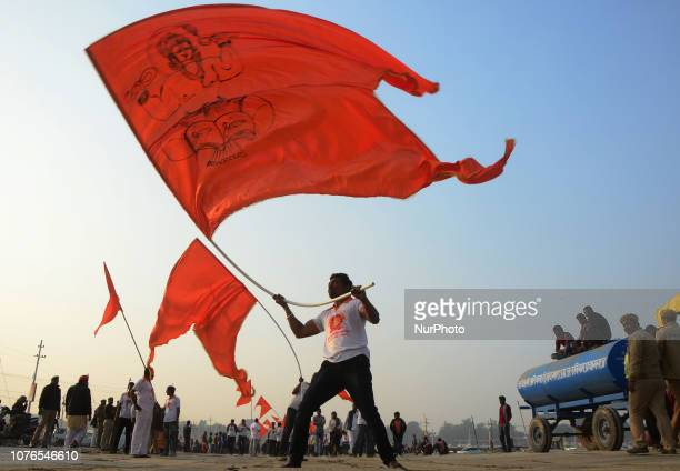 Indian hindu devotees host religious saffron flag during a royal religious procession of 'Niranji Akhara' called ' Peshwai' at sangam , confluence of...