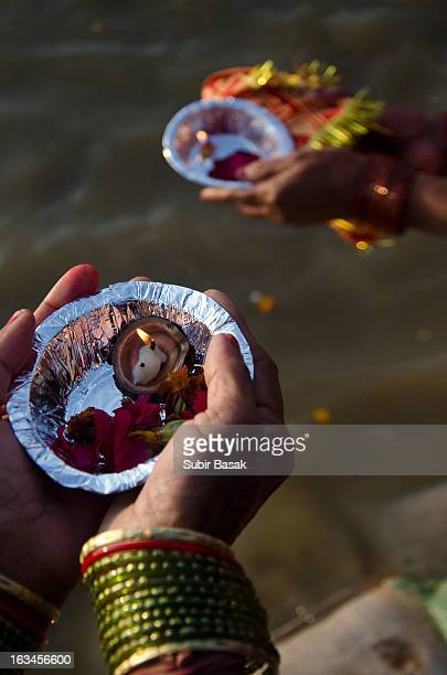 CONTENT] Indian Hindu devotees makes flower with oil lamps offering near the Sangam or confluence of the Yamuna Ganges and mythical Saraswati rivers...