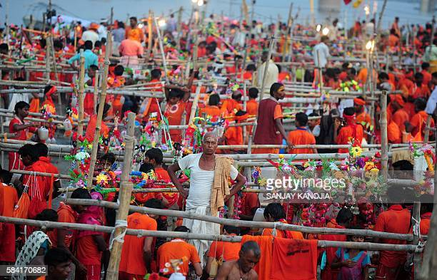 TOPSHOT Indian Hindu devotees of the deity Shiva collect water from the Ganges river for their ritualistic walk towards Varanasi during the holy...
