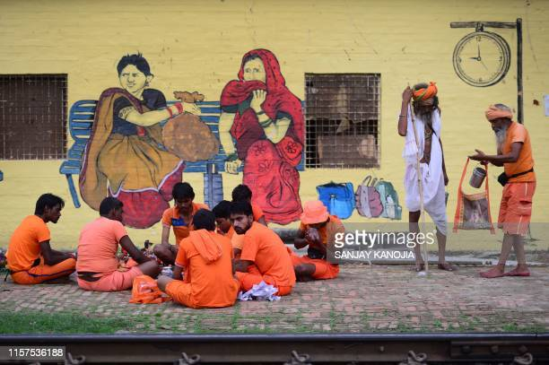Indian Hindu devotees of the Lord Shiva 'Kanwariya' eat food at Daraganj railway station as they arrive to collect water from the Gange river for...