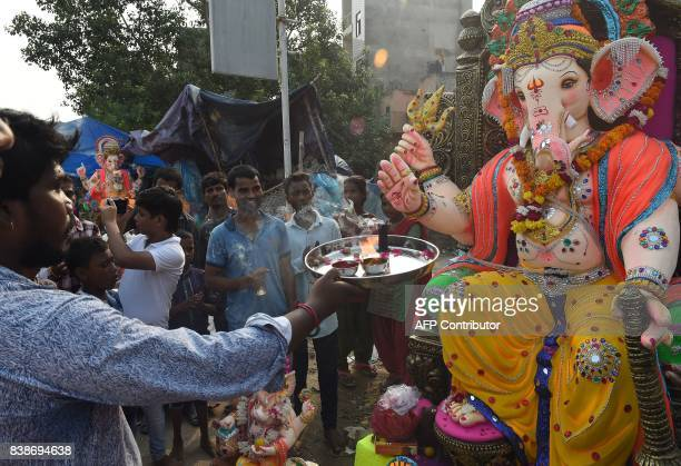 Indian Hindu devotees offer prayer prior to transporting the idol of the Hindu deity Ganesha to their home in New Delhi on August 25 2017 The Ganesh...