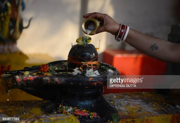 Indian Hindu devotees offer prayers to a Shiva Lingam, a stone sculpture representing the phallus of Hindu god Lord Shiva, to mark the Maha...