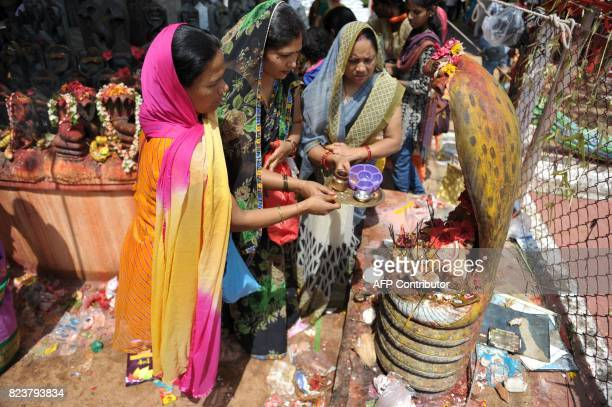Indian Hindu devotees offer prayers to statues of snakes to mark the Nag Panchami festival at a temple in Secunderabad the twin city of Hyderabad on...