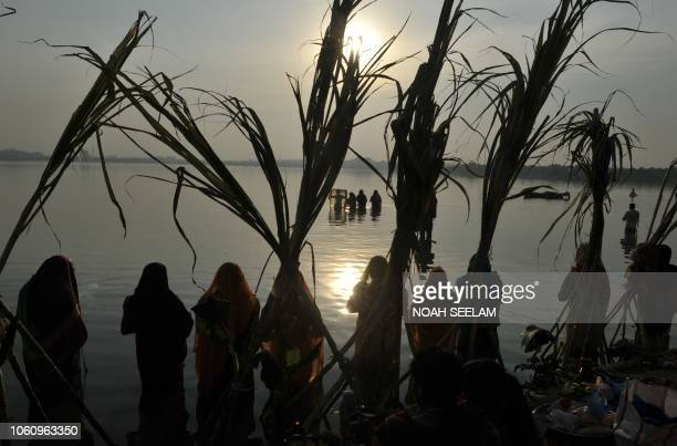 Indian Hindu devotees offer prayers to the sun during the Chhath festival on the banks of the Hussain Sagar Lake in Hyderabad on November 13 2018 The...