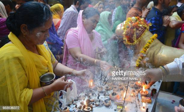 Indian Hindu devotees offering prayers on the occasion of Navratri festival at a temple in Amritsar on March 18 2018 Navratri is celebrated twice a...