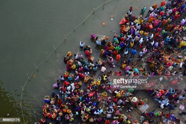 TOPSHOT Indian Hindu devotees perform religious rituals as they offer prayers to the sun god on the banks of the Yamuna river during the Chhath...