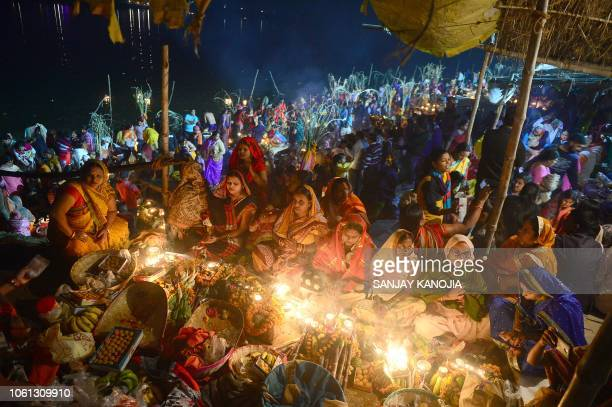 Indian Hindu devotees perform religious rituals during early morning as they wait for the sunrise to pray to the sun god Surya on the banks of the...