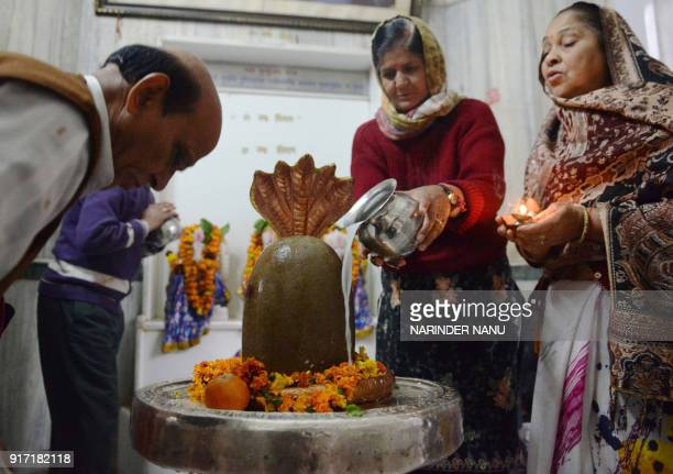 Indian Hindu devotees perform rituals over a lingam representing Lord Shiva at a temple on the eve of the Maha Shivratri festival in Amritsar on...