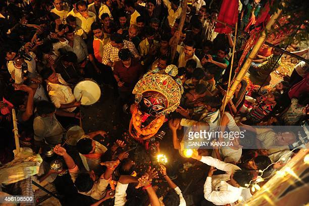 Indian Hindu devotees perform the 'Arti' ritual outside a temple as they offer prayers to an artist dressed as Hindu Goddess Kali during Durga Puja...
