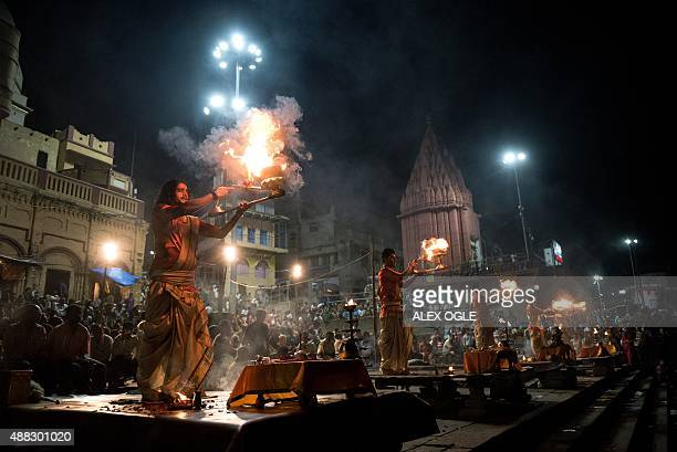 Indian Hindu devotees perform the 'Ganga Aarti' ceremony next to the River Ganges in Varanasi on September 15 2015 The ceremony encompasses an Agni...