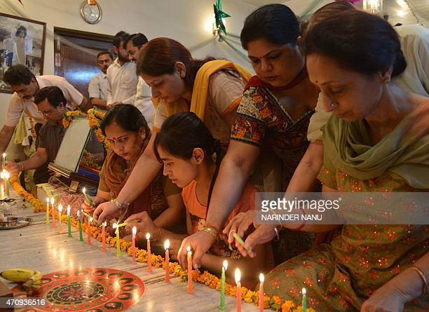 Indian Hindu devotees pose for a photograph as they light candles and offer prayers on the fourth death anniversary of Sri Satya Sai Baba at a temple...