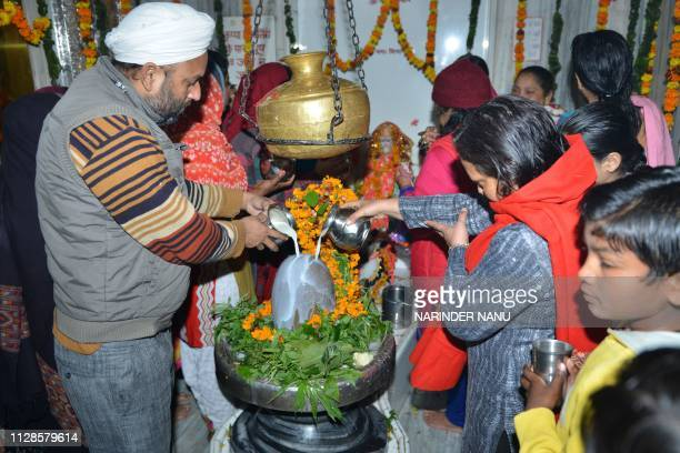 Indian Hindu devotees pour water and milk over a Lingam object representing the deity Shiva at a temple to mark the Maha Shivratri festival in...