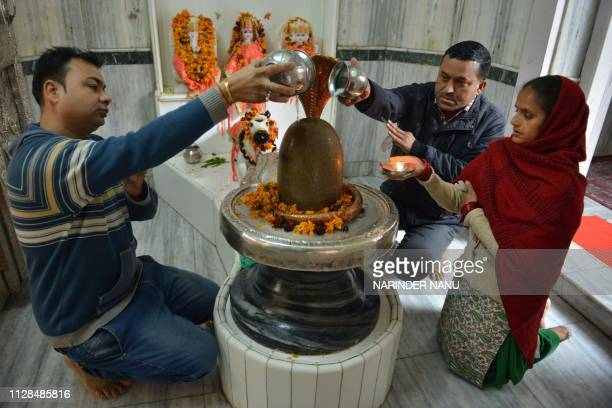 Indian Hindu devotees pour water and milk over a Lingam representing Lord Shiva at a temple on the eve of the Maha Shivratri festival in Amritsar on...