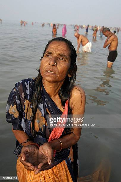 Indian Hindu devotees pray as they stand on the shore of Sagar Island some 150 kms south of Kolkata 13 January 2006 the eve of the main bathing day...