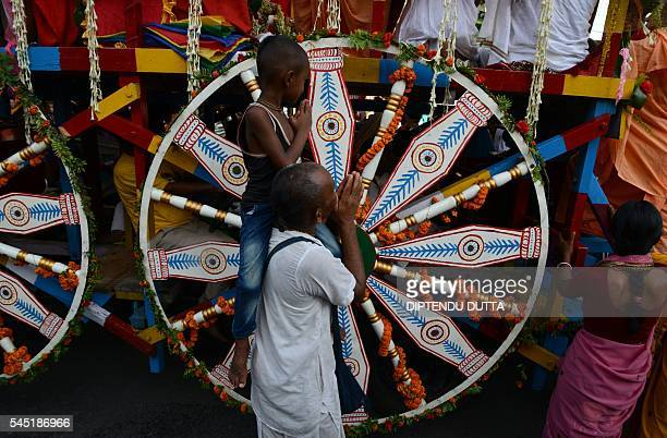 Indian Hindu devoteeS pray at the wheel of a float symbolising Lord Jagannath's chariot during Rath Yatra celebrations in Siliguri on July 6 2016...