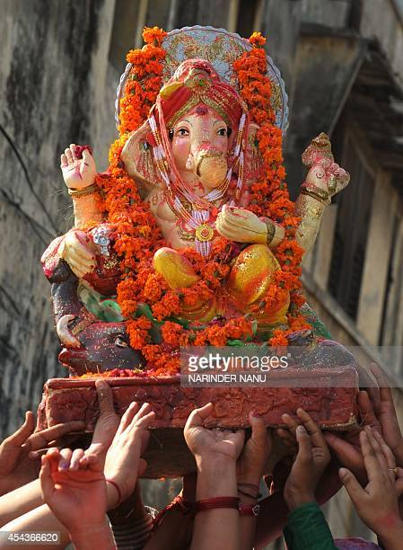 Indian Hindu devotees prepare to immerse a statue of the Hindu god Lord Ganesha on the second day of the tenday Ganesha Festival in a river on the...