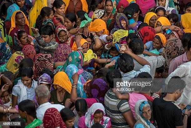 Indian Hindu devotees reach out to receive a blessing from a priest next to the historic Chand Baori stepwell in Abhaneri village in Rajasthan on...