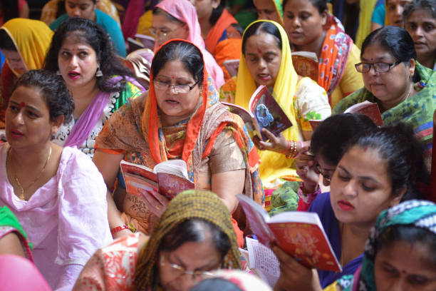 Indian Hindu devotees read a copy of the `Durga Stuti` during prayers for the Navratri Festival at the Mata Longa Wali Devi temple in Amritsar on...