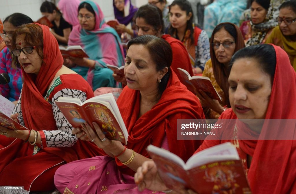 Indian Hindu devotees read a copy of the `Durga Stuti` during prayers on the occasion of Navratri festival at a temple in Amritsar on March 18 2018...