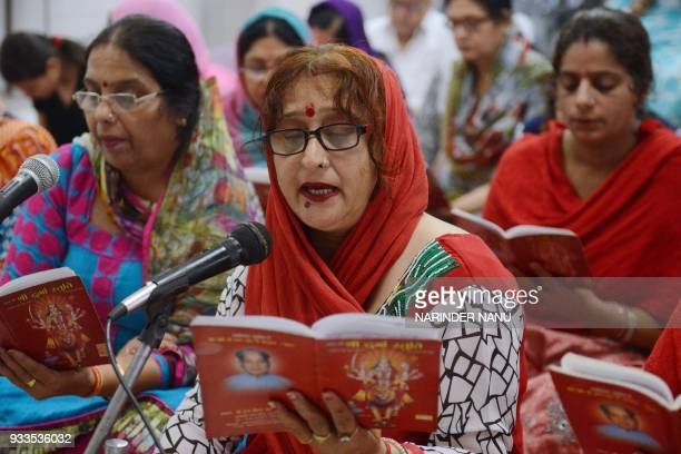 Indian Hindu devotees read a copy of the 'Durga Stuti' during prayers on the occasion of Navratri festival at a temple in Amritsar on March 18 2018...