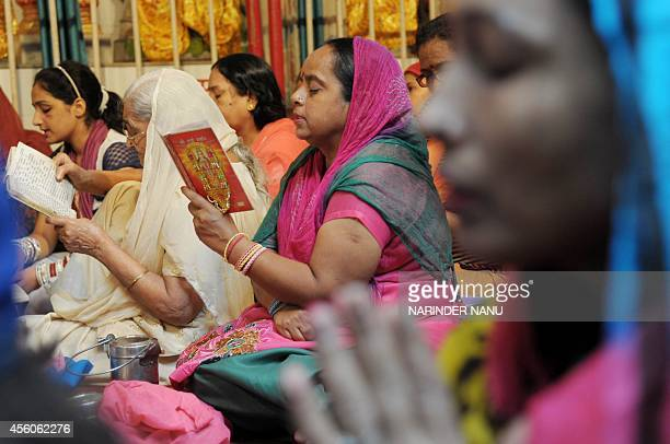 Indian Hindu devotees read the 'Durga Stuati' text during prayers for the Navratri Festival at the Mata Longa Wali Devi temple in Amritsar on...
