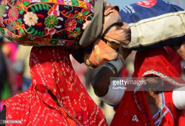 Indian hindu devotees return after taking holy dip at sangam confluence of Ganges Yamuna and mythological saraswati rivers on the auspicious royal...
