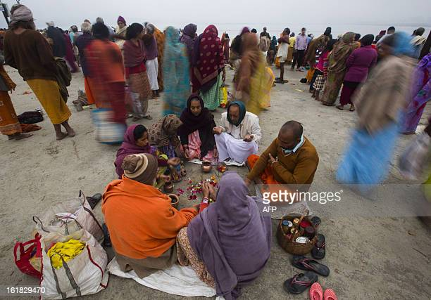 Indian Hindu devotees sit in a circle and perform prayers near the Sangam or confluence of the Yamuna Ganges and mythical Saraswati rivers at the...