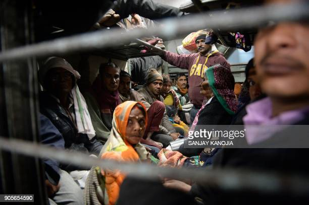 TOPSHOT Indian Hindu devotees sit on a train as they prepare to return home after offering prayers on Mauni Amavasya the most auspicious date for...