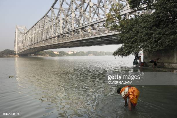 Indian Hindu devotees take a bath in the waters of the Hooghly river in Kolkata in the Indian state of West Bengal on November 16 2018