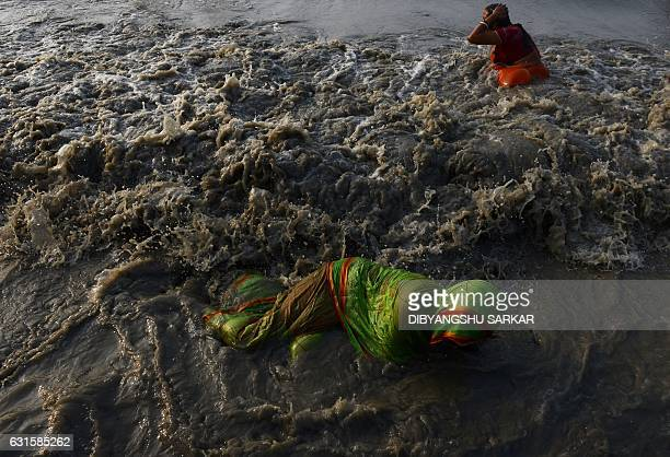TOPSHOT Indian Hindu devotees take a holy bath in the Bay of Bengal at the mouth of the river Ganges in Sagar Island around 150 km south of Kolkata...