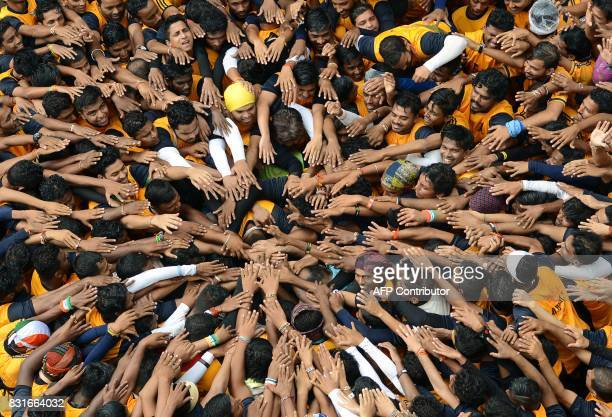 Indian Hindu devotees take a vow before forming a human pyramid in a bid to reach and break a dahihandi suspended in the air during celebrations for...