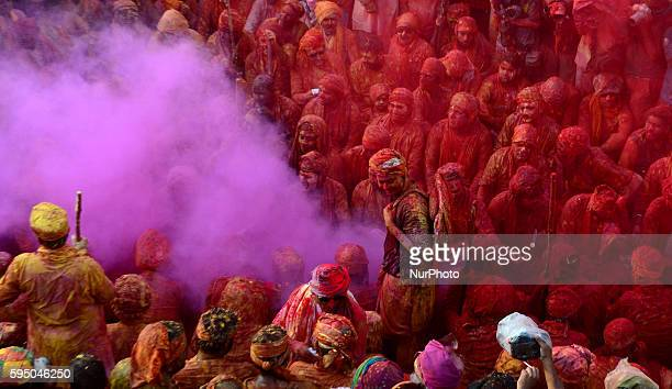 Indian hindu devotees throw colored powder and sing traditional songs called 'Dhamar taal' at Radha Rani Temple during Lath mar Holi in NandGaon some...