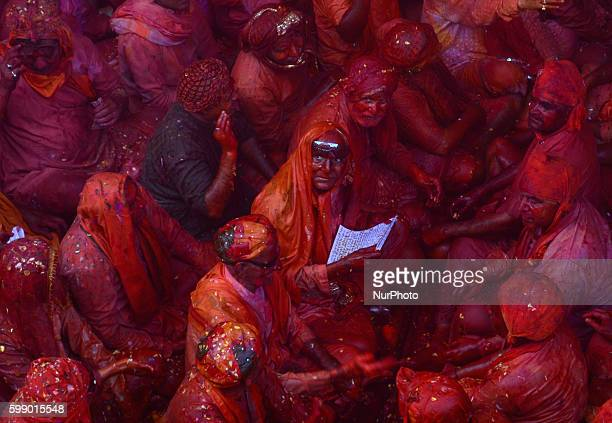 Indian hindu devotees throw colored powder and sing traditional songs called 'Dhamar taal' at Radha Rani Temple during Lath mar Holi in Barsana some...