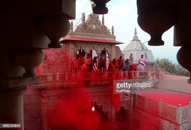 Indian hindu devotees throw colored powder at Radha Rani Temple during Lath mar Holi in Barsana some 43 kms from Mathura on March 172016During the...