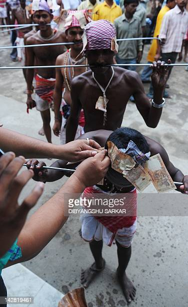 Indian Hindu devotees wait in line to have money pinned to their head scarves after having their tongues pierced with metal rods during the ritual of...