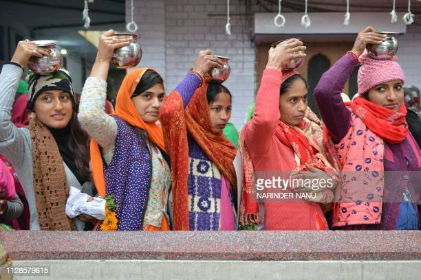 Indian Hindu devotees wait their turn to pour water and milk over a Lingam object representing the deity Shiva at a temple to mark the Maha Shivratri...