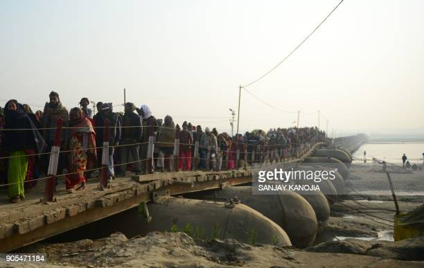 Indian Hindu devotees walk across a pontoon bridge after take a holy dip at the Sangam the confluence of the Ganges Yamuna and the mythical Saraswati...