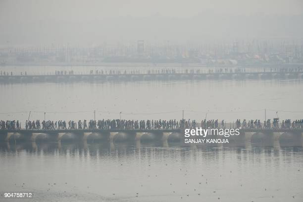 Indian Hindu devotees walk across a pontoon bridge at Sangam the confluence of the rivers Ganges Yamuna and mythical Saraswati during the annual Magh...