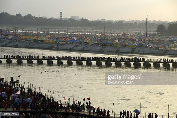 Indian Hindu devotees walk across a pontoon bridge at the Sangam the confluence of the Ganges Yamuna and the mythical Saraswati on the auspicious day...