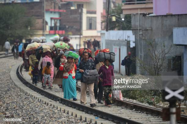 Indian Hindu devotees walk on railway tracks as they return home the day after Mauni Amavasya the most auspicious date for bathing during the Kumbh...