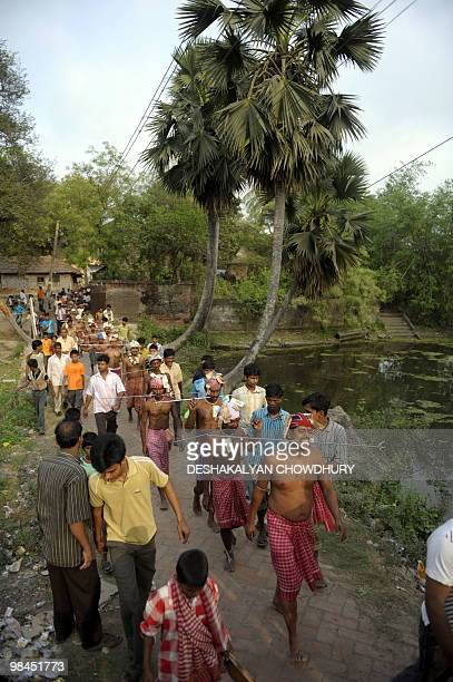 Indian Hindu devotees walk with their tongues pierced with metal rods during the ritual of Shiva Gajan at a village in Bainan some 80 kms south of...