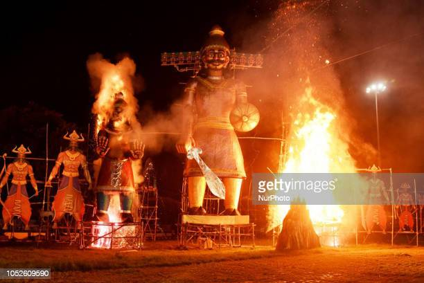 Indian Hindu devotees watch an effigy of the Hindu demon king Ravana stuffed with firecrackers burning in Kolkata on October 19 on the occasion of...